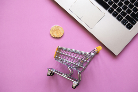 Conceptual photo of e-commerce using cryptocurrency. Computer, shopping trolley and Bitcoin coins or cryptocurrency on a trendy pink background.