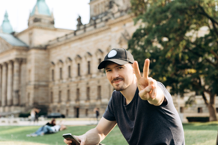 Young man tourist or student sitting on the grass in the streets of Leipzig in Germany and shows the hand gesture means peace.