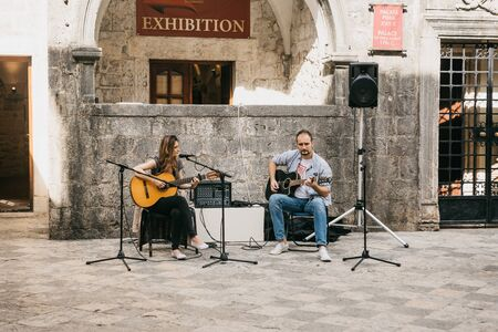 Montenegro, Kotor, June 27, 2018: A couple of street musicians playing guitars for people to make money.