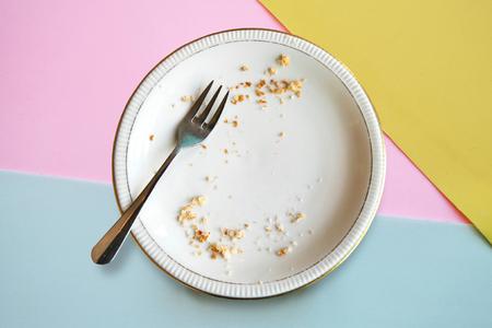 Leerer Teller mit Krümel nach dem Essen auf farbigem Hintergrund. Das Konzept des Endes des Urlaubs oder der Feier.