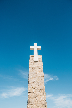 A beautiful view of the Christian Cross at Cape Roca in Sintra in Portugal against the background of a blue sky.