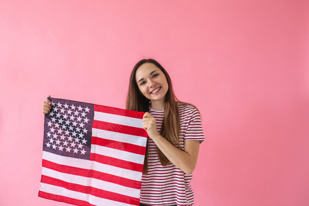 The girl holds in her hand an American flag. A concept of learning American language or immigration or work and travel or the celebration of July 4th