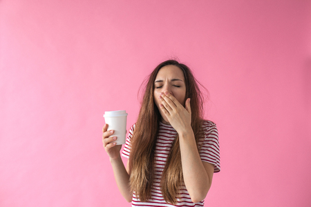 Cute girl with a glass of coffee in hand is yawning. She cant wake up.