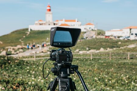 Portugal, Sintra, June 26, 2018: A close-up camera for a photo or a video camera for recording video from Nikon. Ahead is the lighthouse on Cape Roca