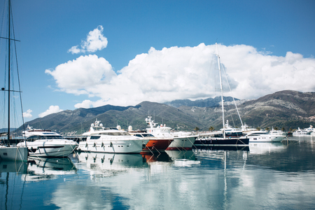 Many yachts moored at the coast in Porto Montenegro in Tivat in Montenegro against the backdrop of a beautiful mountain landscape. Summer sea vacation