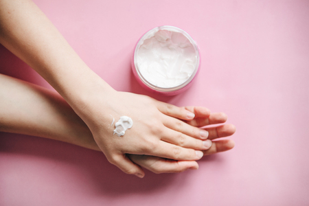 Female hands with cream on a pink background in minimal style. Skin care, beauty and health.