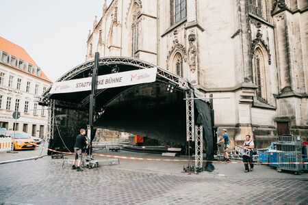 Germany, Muenster, August 17 2018: Workers construct a stage for a concert in the central square. Preparation for the city festival. Editöryel