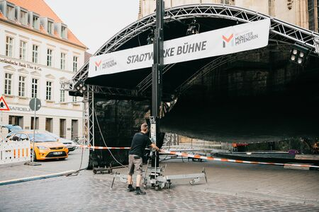 Germany, Muenster, August 17 2018: A worker constructs a stage for a concert in the central square. Preparation for the city festival.