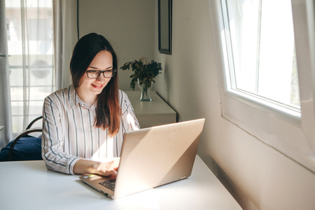 Girl working using laptop in home office. She is reading or learning. Writes a blog or something else. Freelancer at work. The student does the task.