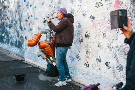 Berlin, October 1, 2017: Authentic photo of a street musician playing an improvised trumpet.
