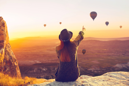 A woman alone unplugged sits on top of a mountain and admires the flight of hot air balloons in Cappadocia in Turkey. Digital detox and soul search Banco de Imagens