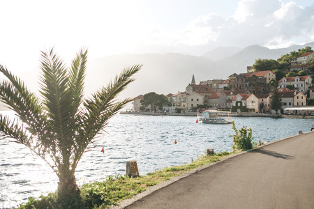 Beautiful view of the ancient architecture in Perast in Montenegro. Boat in the sea and mountains in the background. Sunny day. Stock fotó