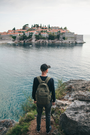 Tourist with a backpack near the sea. Travel alone. Looks into the distance. Ahead is the island of Sveti Stefan in Montenegro.