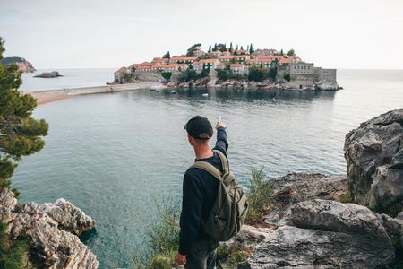 Touriste avec un sac à dos près de la mer. Il montre sa main sur l'île de Sveti Stefan au Monténégro.