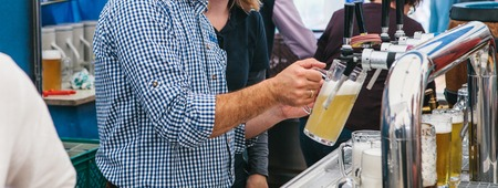The bartender pours a beer into a mug. Brasserie or beer pub or a beer festival celebration.