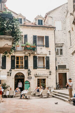 Montenegro, Kotor, May 23, 2019: People eat and rest in a street cafe. Near a street musician plays the guitar.