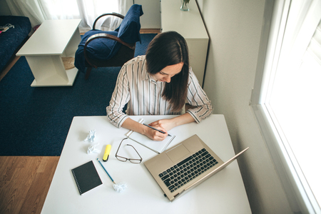 Una giovane e bella studentessa fa i compiti o scrive una lista di cose da fare o questa ragazza lavora in un ufficio a casa. Istruzione a casa o affari o pianificazione.