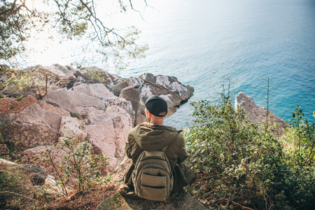 Tourist with a backpack near the sea. Travel alone. Looks into the distance.