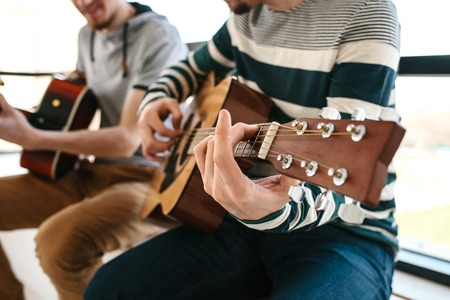 Learning to play the guitar. Extracurricular activities or tutoring or hobbies or creative activities. 免版税图像