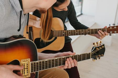 Aprendiendo a tocar la guitarra. Actividades extraescolares o tutorías o pasatiempos o actividades creativas. Foto de archivo