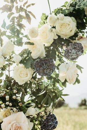 Closeup of flowers, including white roses on a beautiful wedding arch. Preparation for a wedding event.