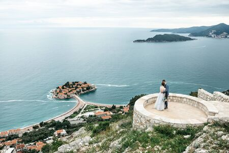 The bride and groom admire a beautiful view of the island of Sveti Stefan in Montenegro.