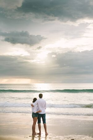 A man hugs a woman. They stand and look at the sea. Solitude together.