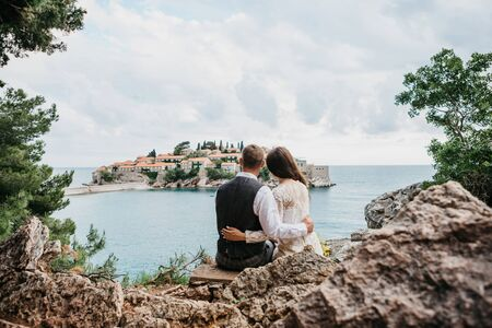 A man and a woman admire a beautiful view of the island of Sveti Stefan in Montenegro. He hugs her.