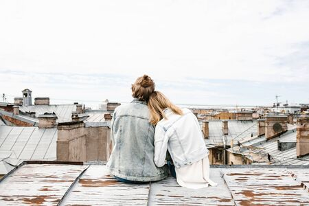 A young couple sits on the roof and admires a beautiful view of the city. Romance, love and trusting relationships. Or he dream or digital detox together.