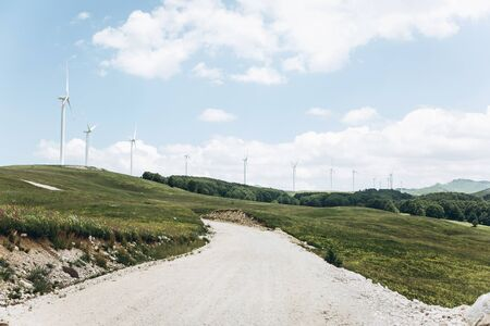 View of the road, natural landscape and sky. Far away windmills. Archivio Fotografico