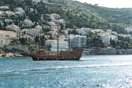 A ship is sailing against the background of old buildings in Dubrovnik in Croatia. Фото со стока