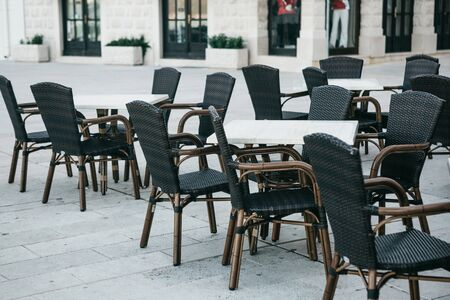 Empty tables and chairs of a street cafe in black and white style