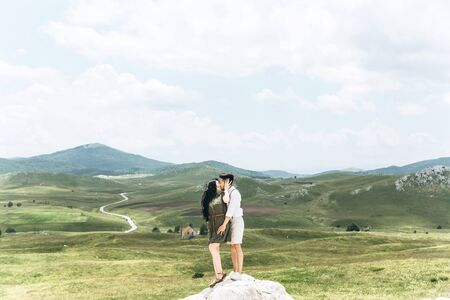Young adult beautiful couple hugs and kisses on the background of a beautiful natural landscape. Фото со стока