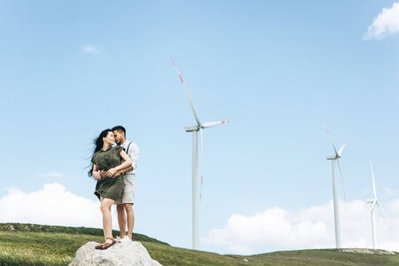 A young couple stands on the background of windmills and hugs. Close relationships and love between people.