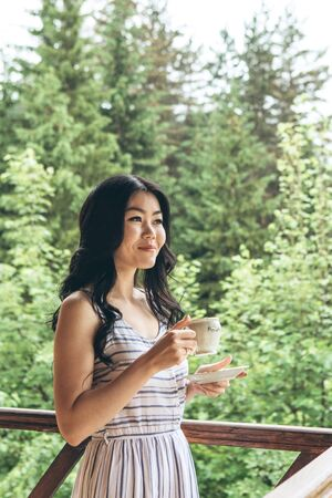Young adult beautiful girl is drinking morning tea or coffee while standing on the balcony.