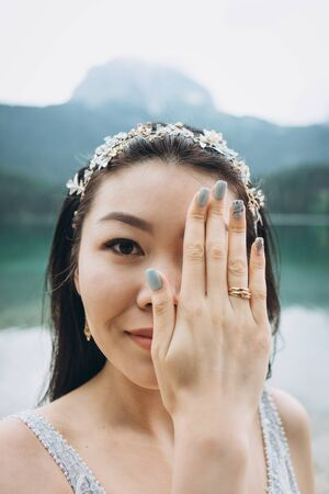 Portrait of a bride with hand covering face. There is a ring on her hand. She just got married and happy.