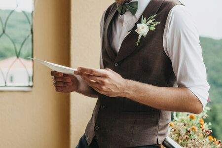 Close-up of a groom holding a sheet of paper in his hands with an oath or invitation. Preparing for the wedding.