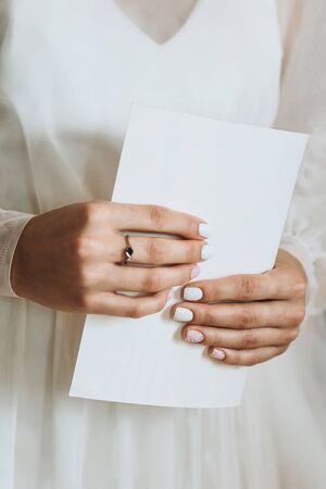 Closeup of brides hand which is a sheet of paper with an oath or invitation. Preparing for the wedding.