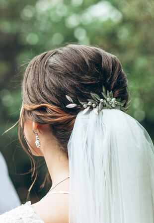 Close-up rear view of bride decorating hairstyle and bridal veil.