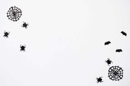 Black spiders and cobweb and bats on a white background. Halloween celebration background.