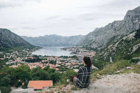 A girl in solitude sits on top of a hill or mountain and looks at a beautiful view of Kotor Bay in Montenegro.