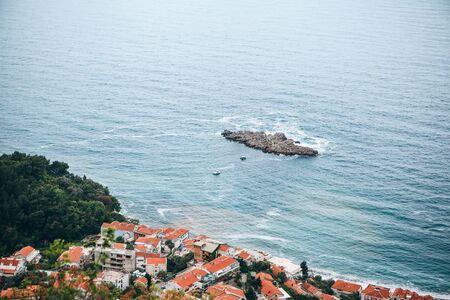 Beautiful birds-eye view of the sea, island and coastal city in Montenegro.