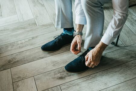 A man in trousers is tying shoelaces on shoes indoors.