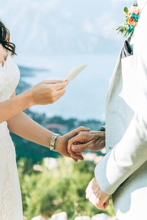 The bride reads her oath to the groom and they hold hands. Stock Photo