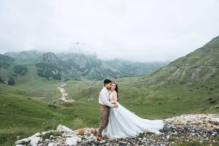 Groom with a bride or couple on a background of a beautiful mountain landscape. Wedding in the highlands.