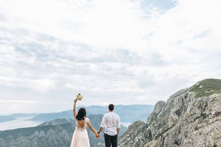 A couple admires a beautiful view of the mountains in Montenegro. They just got married and they have a honeymoon. Tourism and travel.