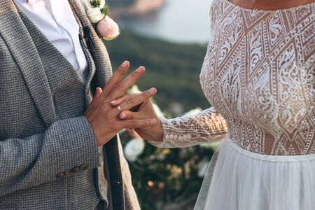 The bride puts the ring on the finger groom. Wedding event. 免版税图像