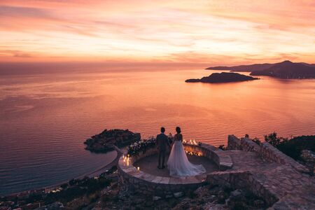 The bride and groom admire the beautiful natural landscape in Montenegro near the island Stock Photo