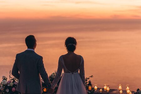 The bride and groom together admire a beautiful red sunset. Stock Photo
