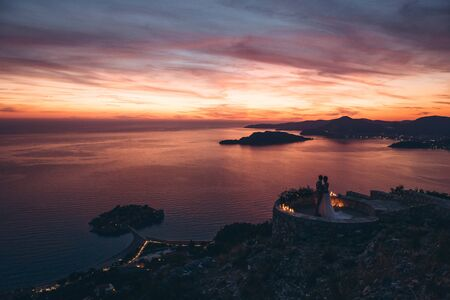Silhouettes of the bride and groom admire the beautiful sunset and natural landscape in Montenegro.
